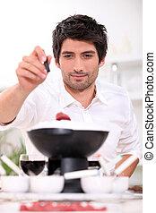 Man dipping raw beef into fondue
