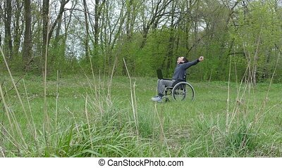 man disabled surprise success victory wheelchair with laptop in wheelchair working on nature green background