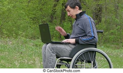 man disabled video chat conversation wheelchair with a laptop in a wheelchair working on nature green background