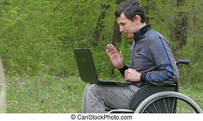 man disabled video chat conversation wheelchair with a laptop in working on nature green background