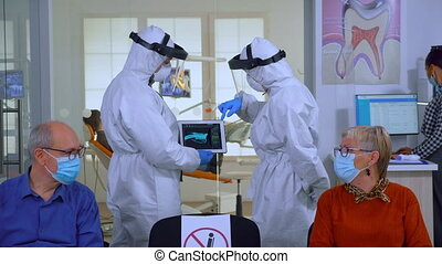 Man discussing with nurse in dental reception wearing protection suit