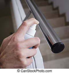 closeup of a caucasian man disinfecting the handrail of an indoor stairway, in an apartment building or office building, by spraying a blue sanitizer from a bottle