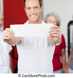 Man Displaying Blank Paper With Group In Background At Gym
