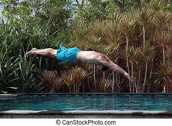 Man dive in blue swimming pool