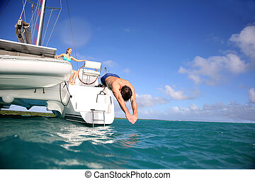 Man diving from catamaran deck into the sea