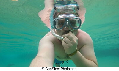 Man diving under water in sea in mask in tropical country