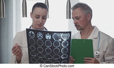 Man doctor and woman talking while looking at x-ray picture in modern clinic.