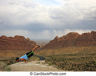Man does balances on hands as he does Mayurasana or Peacock Pose on cliffs of Spotted Wolf Canyon