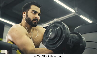 Man Does Biceps Workout - Bearded topless strong man does...