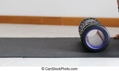 Man does body massage by myofascial roll, to stimulate...