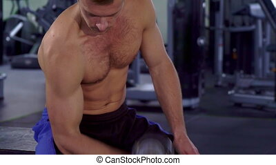 Man does curls with dumbbell