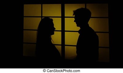 Man does hurting and is hitting his wife. Silhouette. Close...