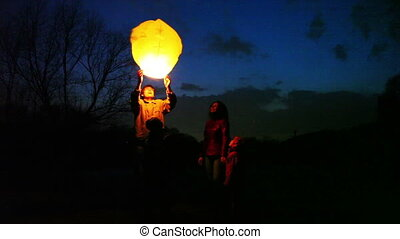 man does some attempts to start glowing chinese lantern, its wife with son and daughter look, part2