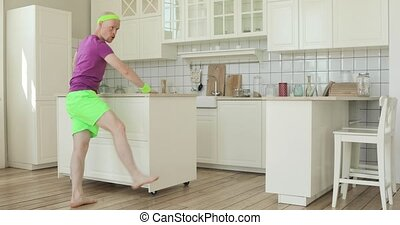 Man does sport exercise for leg in kitchen standing near furniture, sport humor.