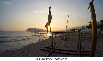 Man doing a One Arm Pull Ups in bea