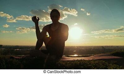 Man doing Ashtanga yoga in the forest at sunset