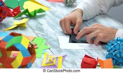 Man doing black origami swan. Lesson of japanese paper...