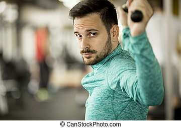Man doing excersise on a lat machine in gym - Handsome man...