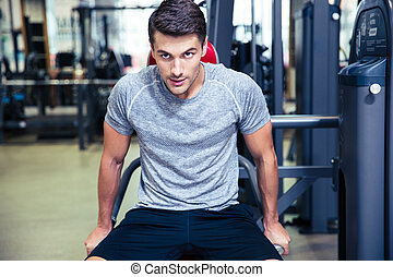 Man doing exercise on a fitness machine in gym