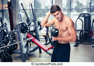 Man doing exercises with dumbbell at gym