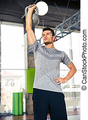 Man doing exercises with kettle ball at gym