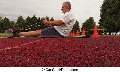 Man doing fitness exercises on stadium