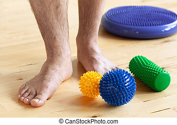 man doing flatfoot correction gymnastic exercise using massage ball at home