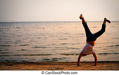 man doing handstand on sunset beach