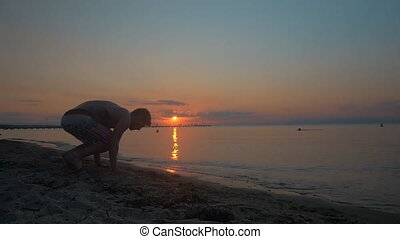 Man doing handstand on the beach at sundown