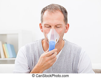 Man Doing Inhalation Through Oxygen Mask At Home