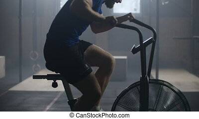 Man doing intense workout on gym bike. Fitness male using air bike for cardio workout at gym