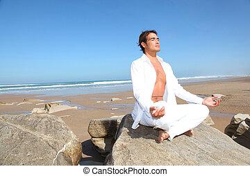 Man doing meditation exercises on the beach