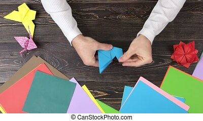 Man doing origami crane, top view. Colored paper sheets and...