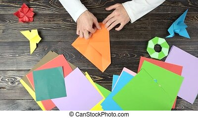 Man doing origami, fast motion. Male hands folding paper...