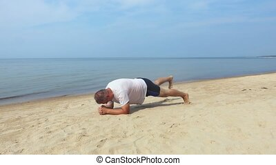 Man doing plank at the sea