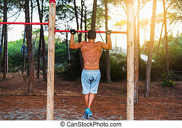 man doing pull ups in a park