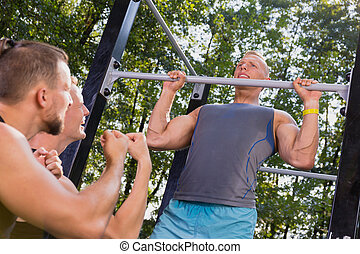Man doing pull-ups in a park