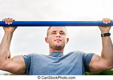 Man doing pull ups outdoors - Masculine man doing pull ups...