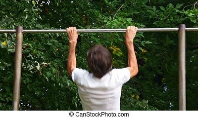 man doing pullups in park