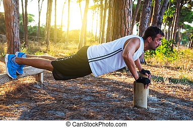 man doing push up in a pine forest at dusk