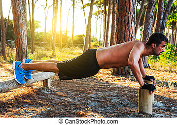 man doing push up in a pine forest