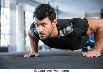 Man doing push ups in gym