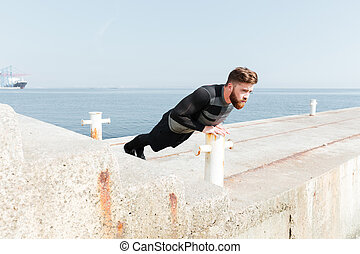 Man doing push ups near the sea