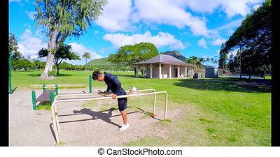 Man doing push-ups on parallel bars at park 4k