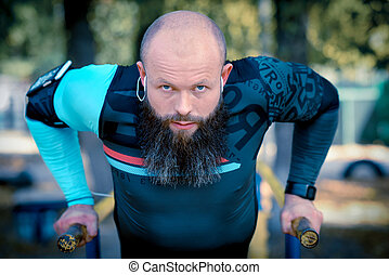 Man doing push ups on parallel bars