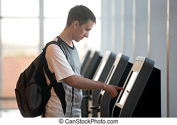 Man doing self-registration for flight - Young man with ...
