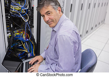 Man doing server maintenance with notebook