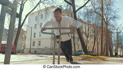 Man doing sports using bike parking rack - Steadicam shot of...