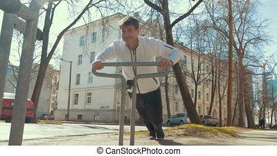 Man doing sports using bike parking rack