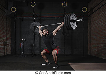 Man doing squats with heavy barbell overhead at the gym